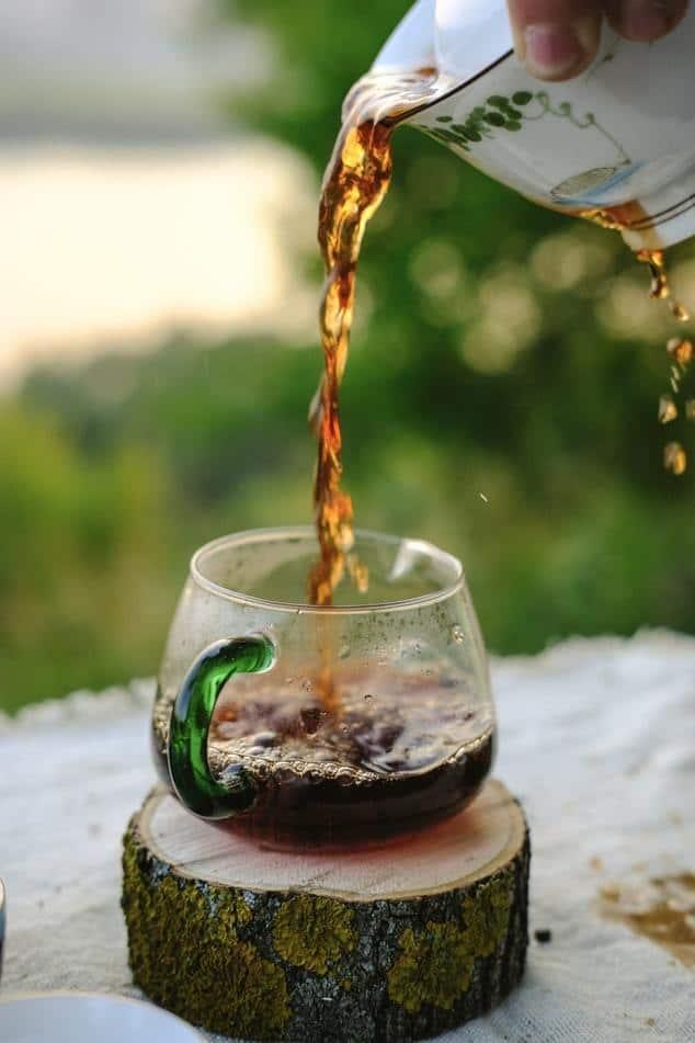 Vertiendo té en un vaso de cristal