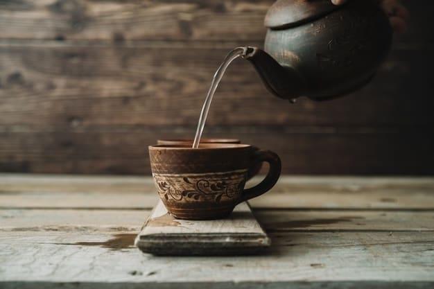Una tetera llenando una taza de té