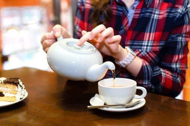 mujer sirviendo té blanco