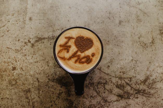 vista cenital de una taza con I love chai escrito con canela