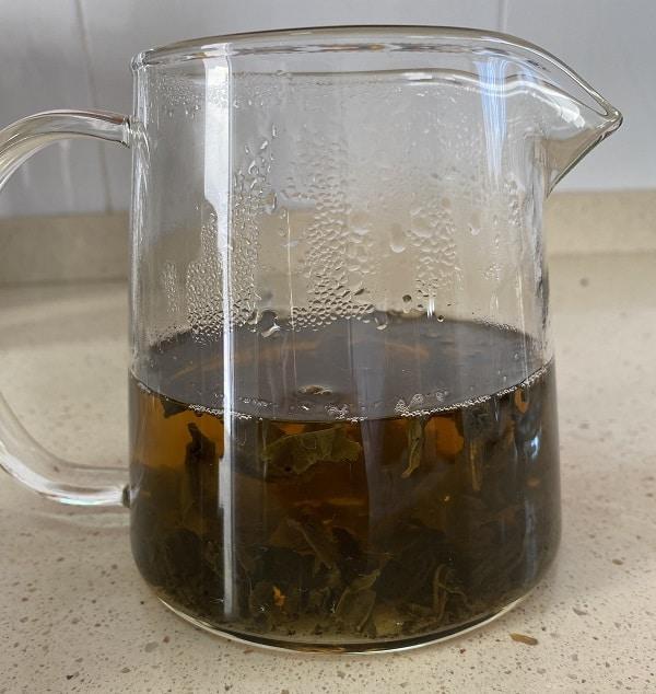 Una tetera de cristal con hojas expandidas de té gunpowder sobre una superficie de granito.