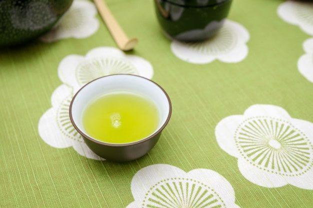 una taza de té verde japonés sencha sobre un mantel verde