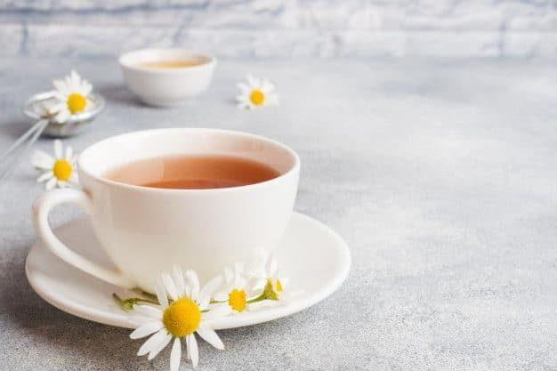taza con té de manzanilla en un fondo gris