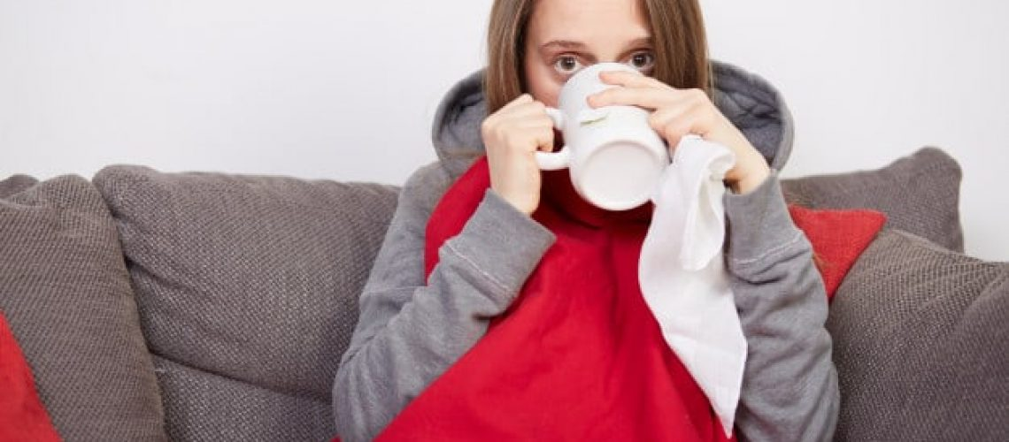 mujer enferma bebiendo de una taza