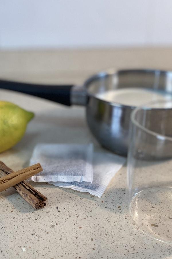 Una olla con leche, un limón, ramitas de canela, bolsitas de té negro y una taza de cristal para preparar té americano,