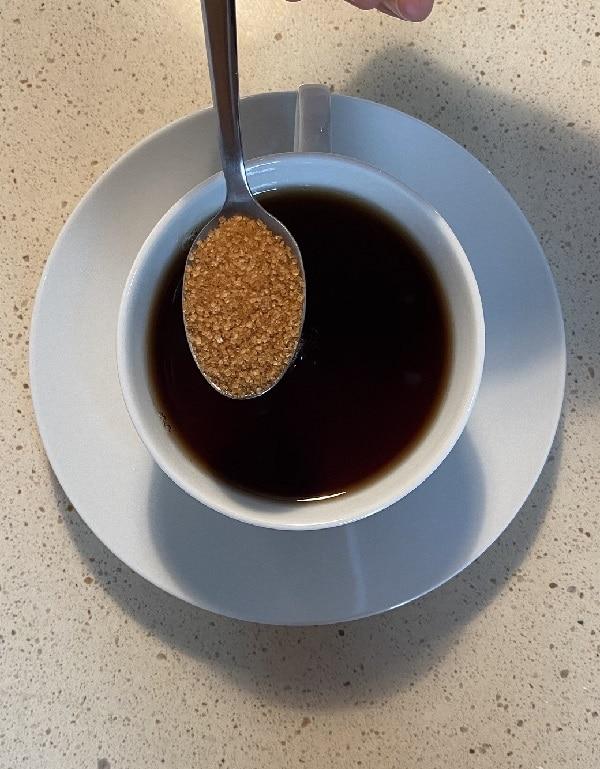 Vista cenital de una cucharada de azúcar moreno sobre una taza de té negro.