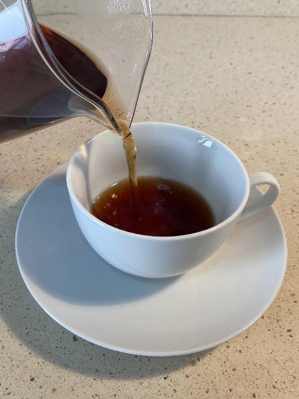Sirviendo desde una tetera de cristal té negro en una taza blanca